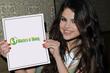 Selena Gomez holding a Masters of Money logo sign.