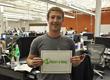 Mark Zuckerberg holding a Masters of Money logo sign.