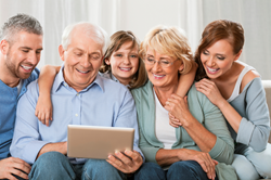 Family enjoying legacy stories on a tablet