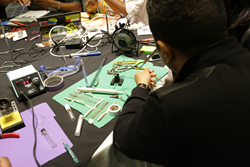 DML Conference-goers making electronic gadgets.