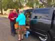 Envoy America Driver Companion Tiago Cruz helps Mrs. Landgren into his vehicle.