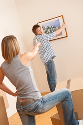 Woman guides man in hanging picture in new home