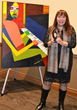 Artist, Soraida Martinez with Cultural Legacy Award and Verdadism painting, Piano Man: The Survival of Hope, in background.