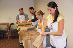 Staff members at Ultimate Medical Academy pack snacks for local school children