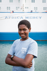 Caleb on the dock in front of the Mercy Ships floating hospital Africa Mercy