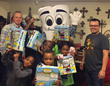 Dr. John U. Bond, Juan Molano & Mighty MolarMan deliver books and plushies to the children at the Samaritan Inn.