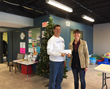 Kelmscott Communications employee Chris Tews presents a $500 check to an Aurora Area Interfaith Pantry representative.