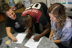 Mo and Alisha Charlo sign a Ziggi's Coffee franchise agreement with Brandon Knudsen, founder of the Colorado-based company.
