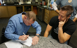 Derrek Kaier (left) signs a franchise deal with Brandon Knudsen (right), founder and president of Ziggi's Coffee