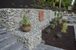 After removing 6-8 feet of blackberry covering a hillside, which is not an easy task, Nyce Gardens added new walls which were made of a mix of block, gabion, and steel and created a sitting area where the homeowner can relax and enjoy views of the lake.