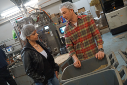 Andrea Garcia (left) tours the Denver-based Coda Coffee Company warehouse with co-founder Tommy Thwaites (right). Coda Coffee Company is the coffee roaster and supplier for Ziggi's Coffee.