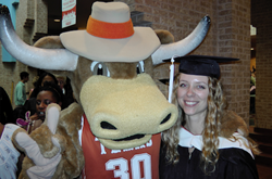 Texas Longhorn mascot with arm around graduating student