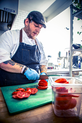 Chef storing freshly sliced tomatoes in Cambro colander food pan.