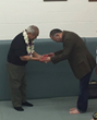 Patrick Burris, Chairman National Promotion Board of USA Judo Presenting the Coveted 9th Degree Black Belt which is actually Red to Coach Willy Cahill