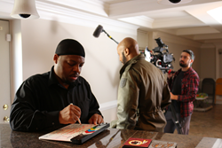 ANACOSTIA's Anthony Anderson marks a clapboard as he prepares to direct a scene of the soap opera.