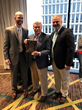 Matt Corso (left) and JJ Dower (right) present the award for Rookie Member Company of the Year to Rick Simpson (middle) of H. Barry Smith Real Estate and Auctioneers