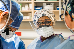 Dr. Odry Agbessi from Benin (center) works alongside surgeons onboard Mercy Ships  as a part of the medical capacity building program offered in her country.
