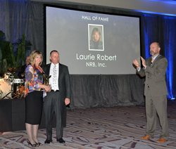 Laurie Robert is presented with the MBI Hall of Fame Award by Bob McNeil, President of NRB Inc. Congratulating Laurie is Tom Hardiman, Executive Director of the Modular Building Institute.