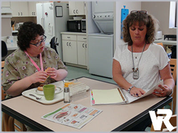 Cheryl Ollis, who is deaf & blind, trains another young woman how to navigate the kitchen