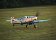 The museum's Messerschmit Bf-109 takes off as the sun sets on the grass runway.