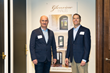 Glenview Haus Owner Greg Wozniak and TruStile President and CEO Scott Schmid stand in front of a sign for the Glenview Haus showroom