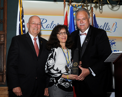 Janis Grover (C), president of Grover Global Food Marketing, receives District 7510 Rotarian of the Year Award from David Breidinger (R), award committee chair, and Michael Townley, district secretary (L).
