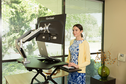 This versatile sit-stand desktop riser can be used on either a corner desk or a standard table. It comes with an adjustable tilting document holder that can hold documents, a tablet, or a laptop. It also features a quick-release keyboard tray with multipl