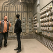 Jonas Villalba, VP of Project Development with Promise Energy, demonstrates the complexity of the installed conduit runs from Olympic's individual PV systems.