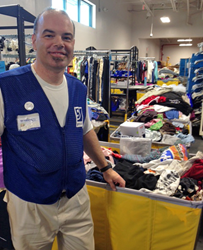 Photo of James Molonson with cart of donated clothes at his job at Goodwill