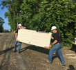 Tony Cananaco (L) and Tom Rosenberg (R) carry materials to the job site.