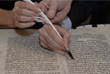 A close up of a person writing a ceremonial letter during Calvary's year-long effort to restore a 135-year-old historic Torah Scroll.