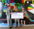 Principal Mario Romero receives donation from Collier and Hoben on behalf of Discovery Canyon Middle School Band