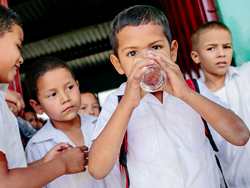 A group of of Honduran children take turns sampling the clean drinking water filtered through a Sawyer PointONE clean water filter.