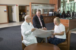 Sue and Terry McGraw meet with Jonathan Fine, MD (left), to review plans for the new McGraw Family Center for Advanced Learning