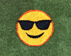 The smiling face with sunglasses emoji Funsert from ForeverLawn is one of eight new designs that provide a splash of color and imagination to playground projects.