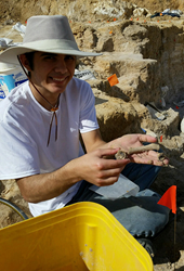 Photo of Trey Hall holding a fossil at a dig in Florida
