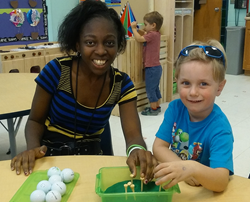 Photo of Kelsey working on a project with a preschool student.