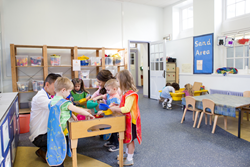 Children Interacting at Sensory Tables in Classroom