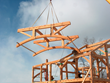 "A parallel truss with curved bottom chords is ""flown"" into place by New Energy Works craftsmen."