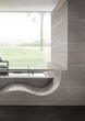 Spa-style bathroom featuring bath, wall cladding and chaise lounge in Corian® Ash Concrete