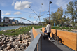 "A pedestrian bridge provides access to the award-winning park from downtown Calgary's East Village neighborhood and provides views of the Michel de Broin public art sculpture ""Bloom"" and the city beyo"