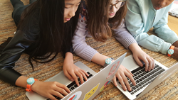 Girls writing code for their Jewelbots Bracelets
