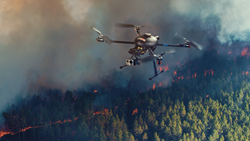 A small UAV is shown surveying the movement of a forest fire.