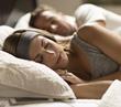 a couple wearing SleepPhones headphones in bed