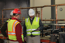 The TG Gallagher team in the fabrication shop is discussing when an item is scheduled to be delivered to the jobsite, and checking the production status for the item.