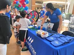 Andrews Federal's Ryan Drigo looks on as two young attendees spin the wheel for a prize at the Back2School Bash at Springfield Town Center.