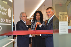 Pano Yeracaris, Janet LaBreck, and Clifford Scott standing by red ribbon with scissors for ribbon cutting ceremony.