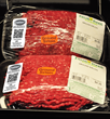 Packages of prewrapped ground beef with the SaniTrace labels.