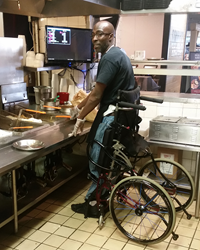 Theo works in the kitchen of Sonny's with the help of his stand-up wheelchair.