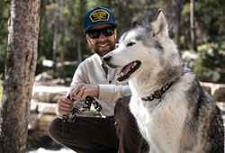 Loki The Wolfdog wearing the LokiWolf Collar and Kelly holding the LokiWolf leash, sitting in the woods.